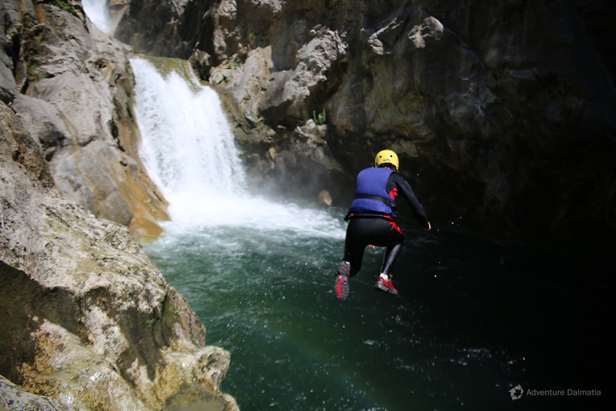 Jumping from the rock into the lake below Velika Gubavica waterfall, Cetina river
