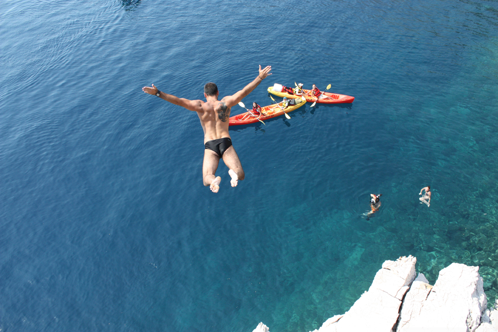 Jumping from the cliff on a sea kayaking tour in Brela