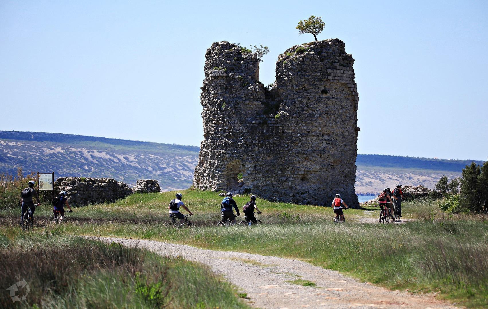 Old stone tower on a pebble beach by the sea - Večka kula
