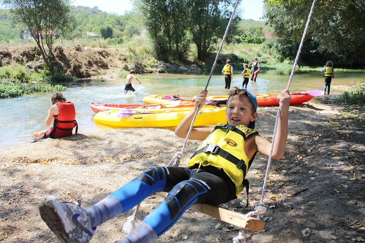 Kids playing during the break on Canoe safari. Vrljika river near the town of Imotski.