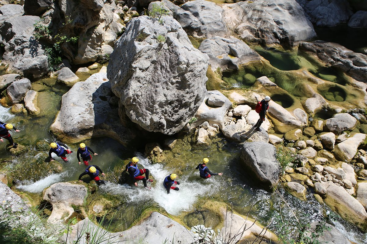 One by one, following the guide on a Canyoning tour