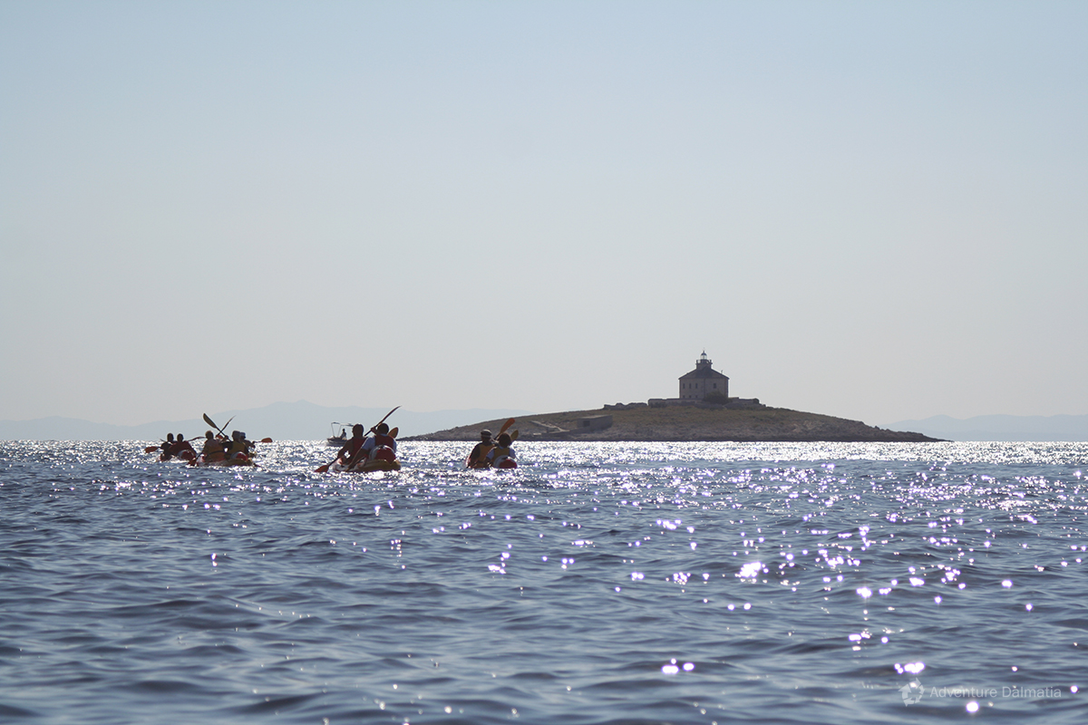 Sea kayaking near the lighthouse in front of town Hvar