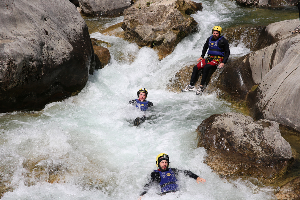 Sliding into the rapid one by one on Extreme Canyoning tour