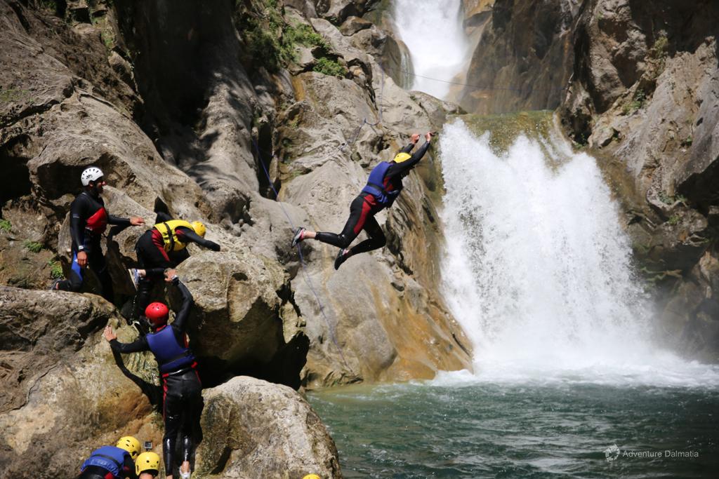Taking a break to jump near the waterfall